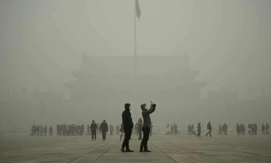 A visitor takes a photo in Tiananmen Square during heavy pollution in Beijing on December 1, 2015. Smog is being blamed for recent downturn in tourists.