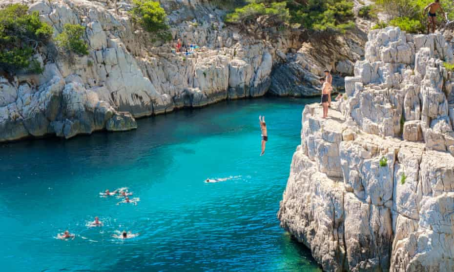 People jumping into beautiful blue water from a rocky outcrop at Calanque de Sugiton