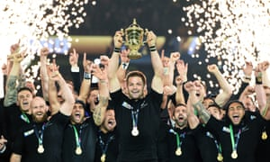 New Zealand's rugby union captain, Richie McCaw, lifts the Webb Ellis trophy, surrounded by his cheering team mates