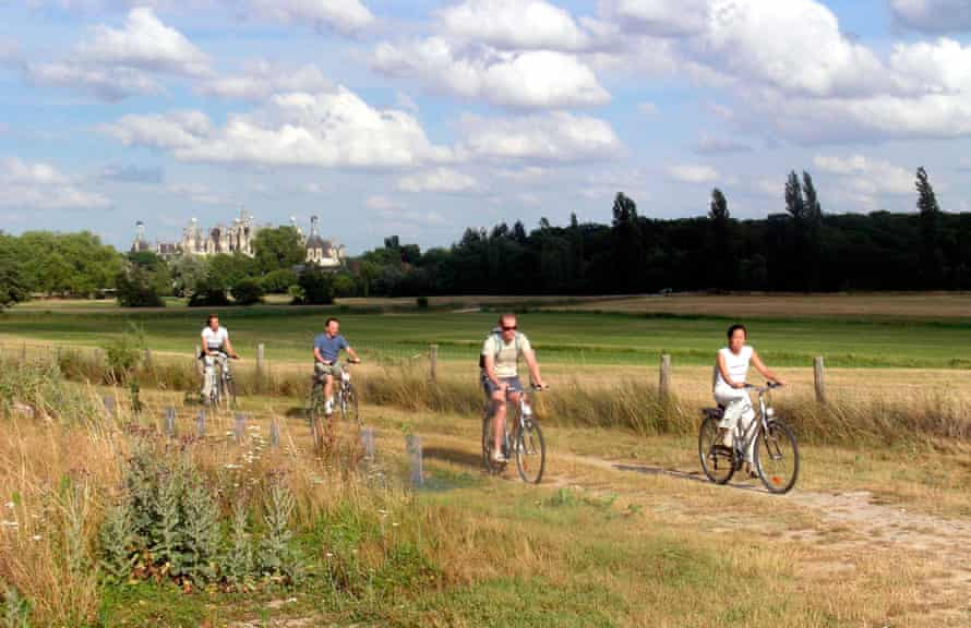 A family cycling in France through a field.