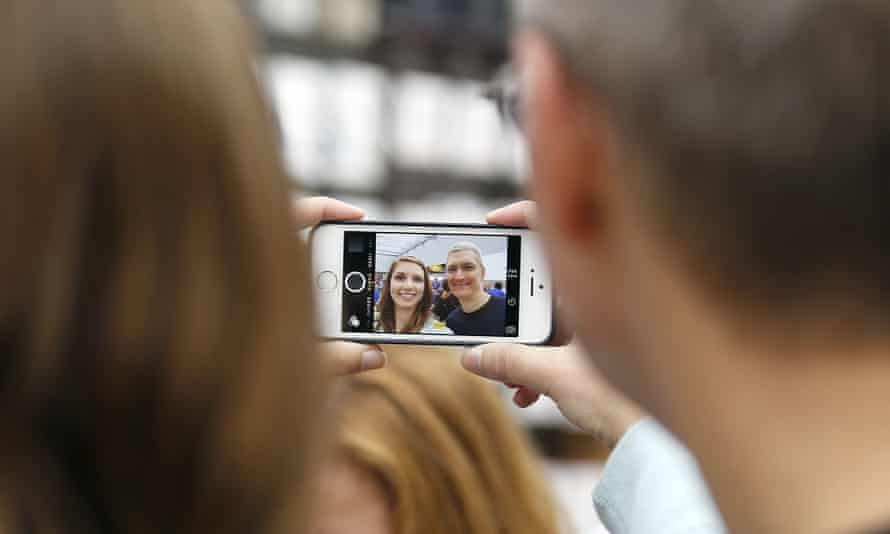 Apple CEO Tim Cook, right, takes a photo with an Apple employee