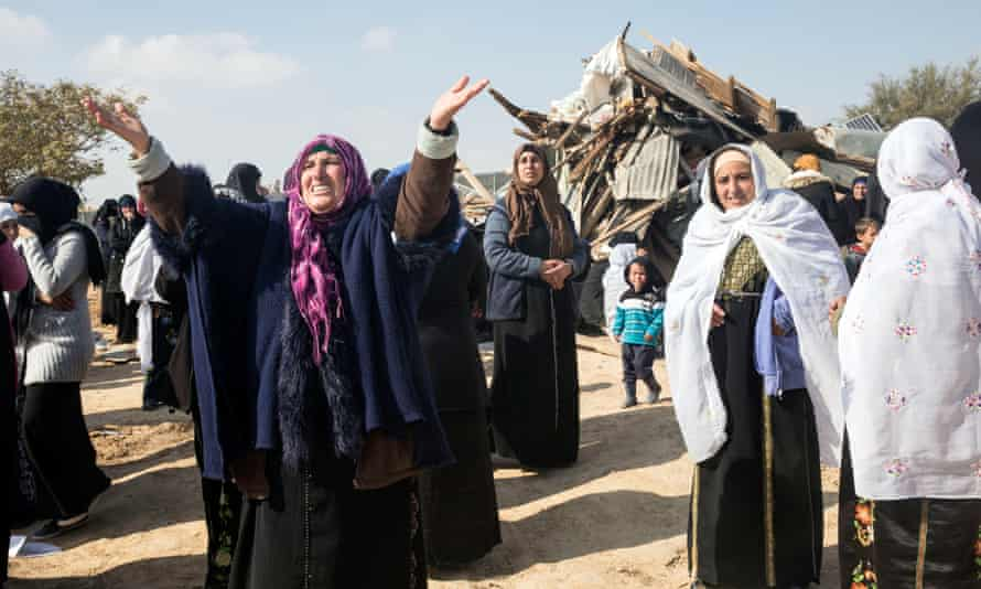 Bedouin villagers gather outside a destroyed building in Umm al-Hiran.