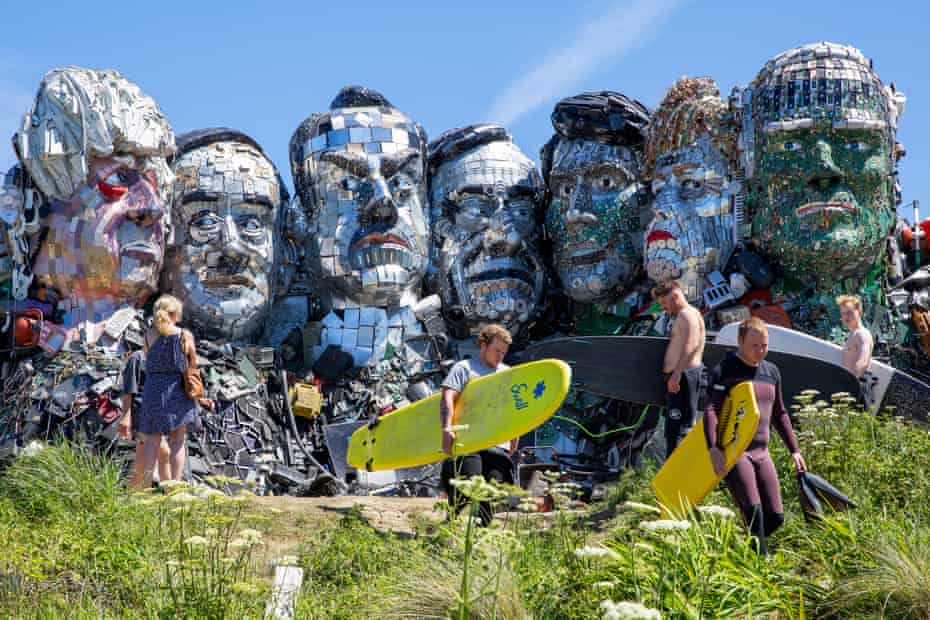 Surfers passing by 'Mount Recyclemore' in Hayle, a monument of the G7 leaders built from old technological waste