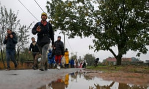 Migrants walk along a road after crossing the border with Serbia in Bapska, Croatia, on Monday