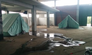 Tents are pitched on filthy concrete floors