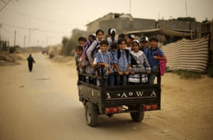 Palestinian schoolchildren ride a motorcycle rickshaw in Khan Yunis in the southern Gaza Strip