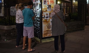 People look at photographs of missing persons in a phone box near where the fire broke out at Grenfell Tower.