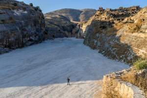 Çetin Yıldırımer, known as Mazlum, a 28-year-old tourist guide, stands in the middle of the now-demolished ancient town of Hasankeyf at sunrise, on the banks of the Tigris. Yıldırımer will loose his job, as the waters come to cover to the area.