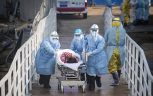 Medical workers in protective suits help transfer suspected coronavirus patients into the Huoshenshan temporary field hospital in Wuhan, in central China's Hubei province