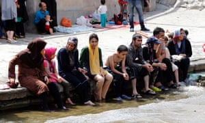 A group of Iranians sit with their feet in a pool.