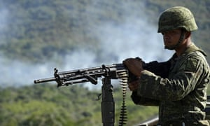 A Mexican soldier of the 88th infantry brigade patrols as smoke rises after a military helicopter was shot down in Jalisco on Saturday.