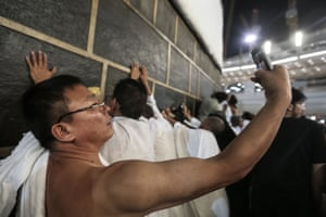 A pilgrim takes a photograph next to the Kaaba