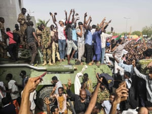 Demonstrators stand on an army armoured military vehicle as they cheer and flash the sign of victory
