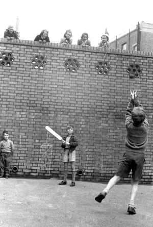 A boy playing street cricket with his friends, watched by five little girls