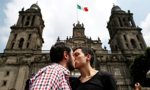 A couple kiss each other in front of the cathedral during a march in support of gay marriage, sexual and gender diversity in Mexico City on 11 September 2016.