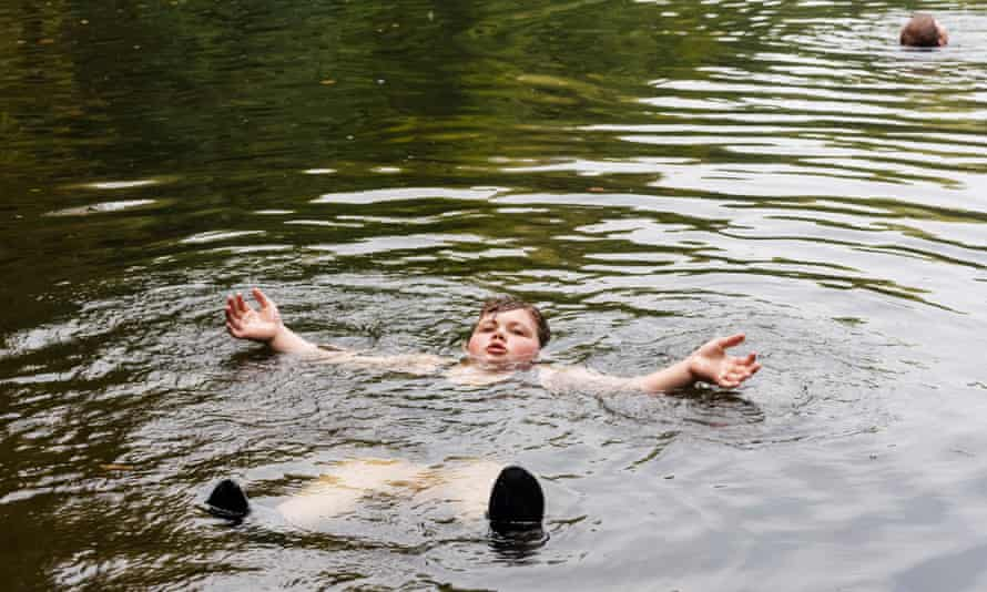 A boy called Dominic floating on his back in a lake while wild swimming