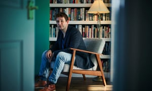 Andrew Hankinson at home in Newcastle, sitting forward in a comfy chair, a full bookcase behind him