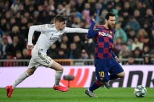 Barcelona's Argentine forward Lionel Messi (R) vies with Real Madrid's Uruguayan midfielder Federico Valverde.