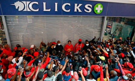 Julius Malema with a group of supporters outside a shuttered Clicks store