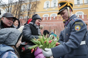 A serviceman of the Presidential Regiment gives flowers to women after performing in the Alexander Garden by the Kremlin wall in Moscow, Russia