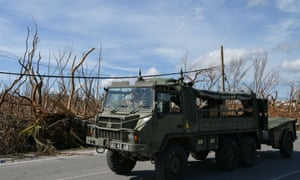 Military personnel drive past damage in the wake of Hurricane Dorian in Marsh Harbour, Great Abaco, Bahamas, on Sunday.