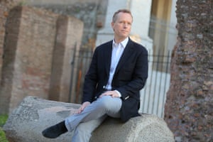 edward st aubyn sits for a photo outside near some ruins in rome