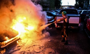 A man attempts to put out a fire in a parking lot during a demonstration in Minneapolis, Minnesota.
