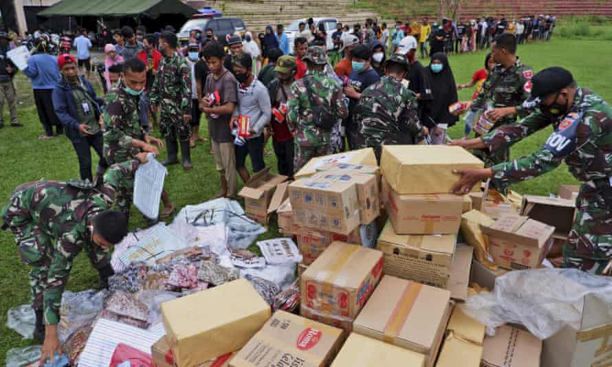 Indonesian soldiers distribute relief goods for those affected by the earthquake at a stadium in Mamuju, West Sulawesi, Indonesia.