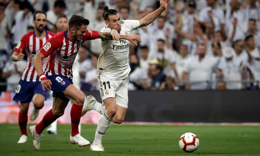 Gareth Bale of Real Madrid jostles with Atlético Madrid's Saúl Ñíguez during the goalless Madrid derby.