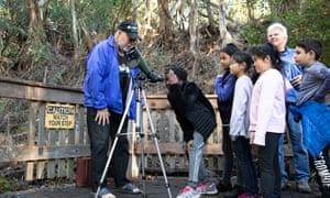 Glen Cornett, a retired math teacher who volunteers at Natural Bridges grove in Santa Cruz, uses a scope to show children a cluster of butterflies.