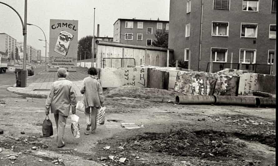 Berliners walk among the ruins of the Wall.
