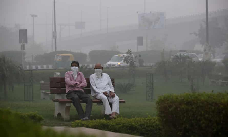 Two men cover faces in polluted New Delhi