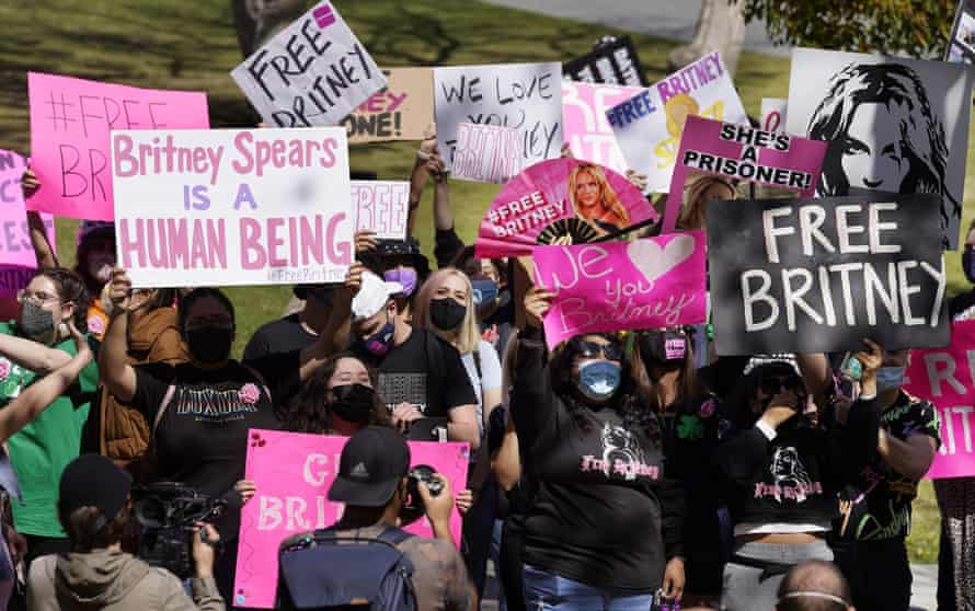 Britney Spears fans hold signs outside the Los Angeles courthouse where the pop singer's conservatorship hearing was being held on 17 March.