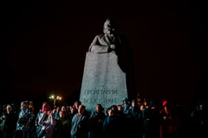 Visitors of the Circle of Light international festival watch the lighting installation while standing in front of a Karl Marx monument