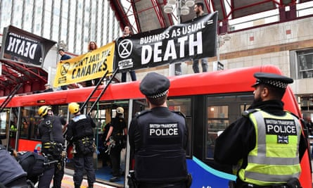 Police preparing to remove climate change activists on the roof of a DLR train at Canary Wharf station on Thursday.