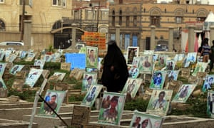 A Yemeni woman walks amongst portraits on the graves of Houthi militia members allegedly killed in fighting in the war-torn Arab country, at a cemetery in Sana'a.