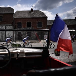 A French national flag flies on a convertible car as riders pass by during the third stage between Binche and Epernay.