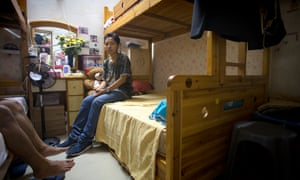 Roy Wardha sits on bunk bed in apartment she shares with 11 others in Macau's Sam Can Tang neighbourhood