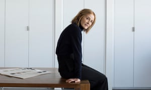Caroline Belhumeur sitting on a desk with a swatch on it, white cupboards behind her