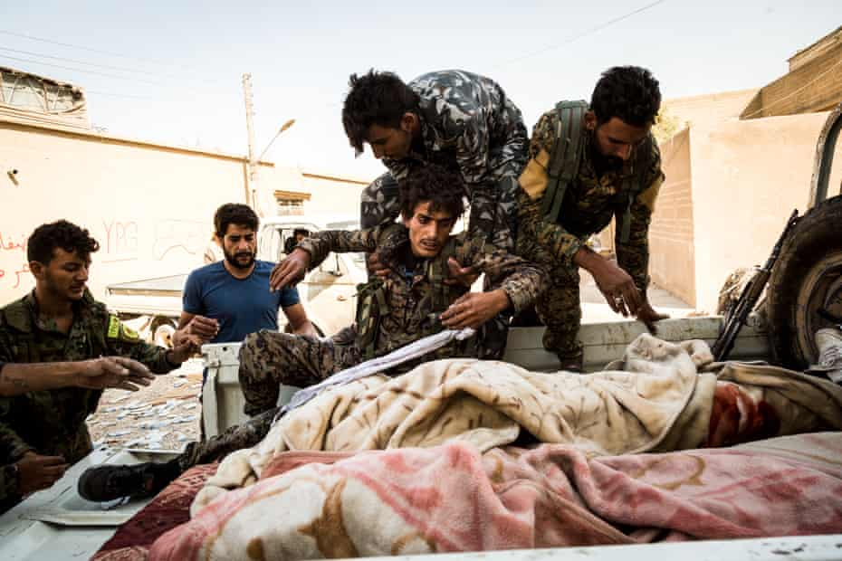Syrian Democratic Forces fighters help a wounded comrade on to the back of truck in Raqqa.