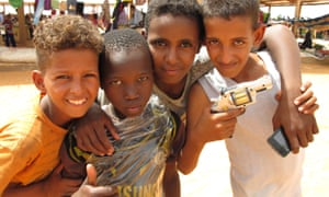 Boys pose with a toy gun at the marketplace in Mbera refugee camp
