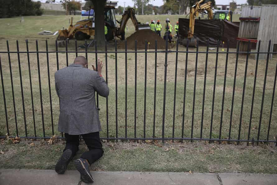Rev Robert Turner, of Vernon AME Church, prays as crews search for remains at Oaklawn Cemetery in Tulsa, in October 2020.