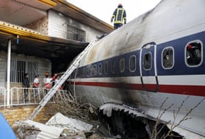 Emergency services work at the scene of the wreckage of a Boeing 707 cargo plane that crashed while landing at Fath airport.