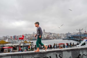 A child walks barefoot across a wall at Eminonu Square in Istanbul, Turkey