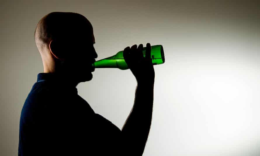 Middle aged man in silhouette drinking from a bottle