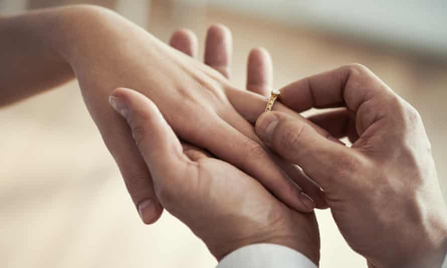 Close-up of a man placing a wedding ring on a woman's finger