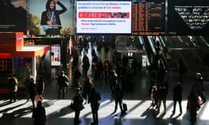 People walk past a 'clock' displaying Italy's public debt in Termini station, Rome.