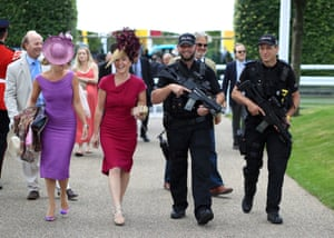 Goodwood, UK Two racegoers get an armed escort into the Goodwood festival on opening day