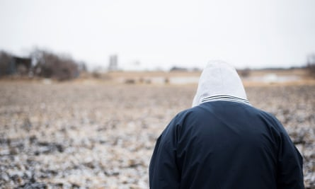 anonymous person with hoodie walking in field