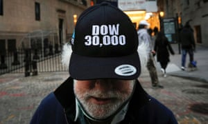 Trader Peter Tuchman wears a DOW 30,000 hat outside the New York Stock Exchange (NYSE) in New York.